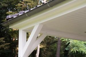 Terrassenüberdachung aus Leimholz, weiß gestrichen, und einer Dachziegeln in schwarz.