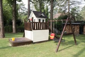 Spielhaus mit Schaukel, Rutsche und Sandkasten von der Seite
