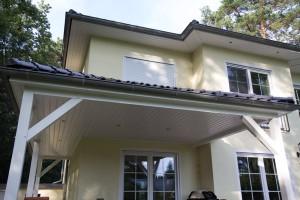 Terrassenüberdachung aus Leimholz mit schwarzen Dachziegeln.